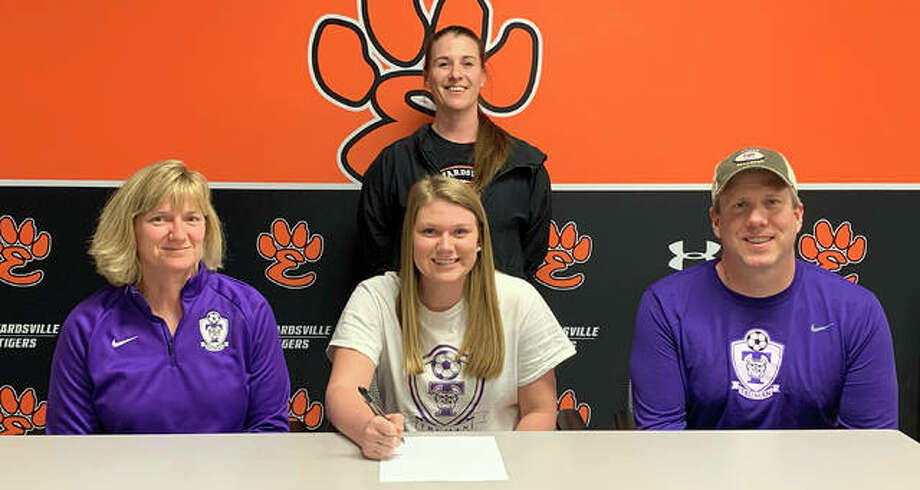 Edwardsville senior Casey Hansen, seated center, will play college soccer at Truman State. She is joined by her family and EHS coach Abby Federmann. Photo: Matt Kamp|The Intelligencer
