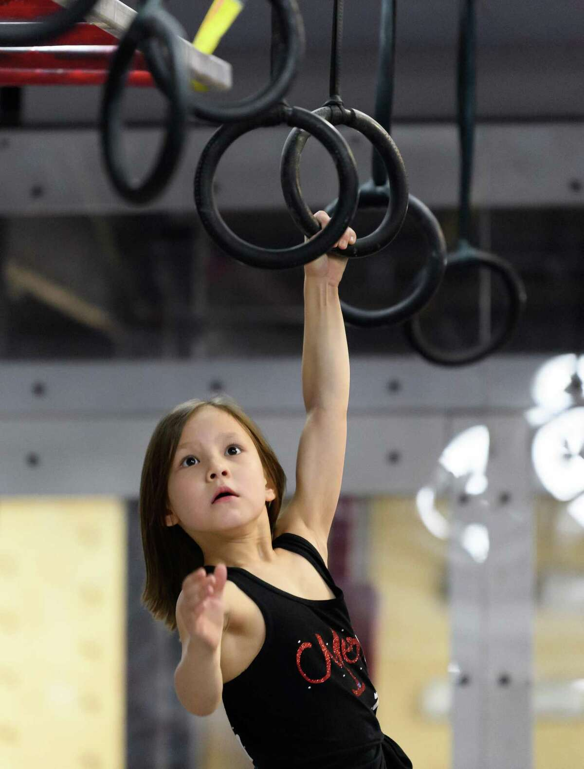 7 year old Maeleigh Kim, Meredith Kim's younger sister works on the Rings on Friday, March 6, 2020 at Iron Sports in Houston Texas.