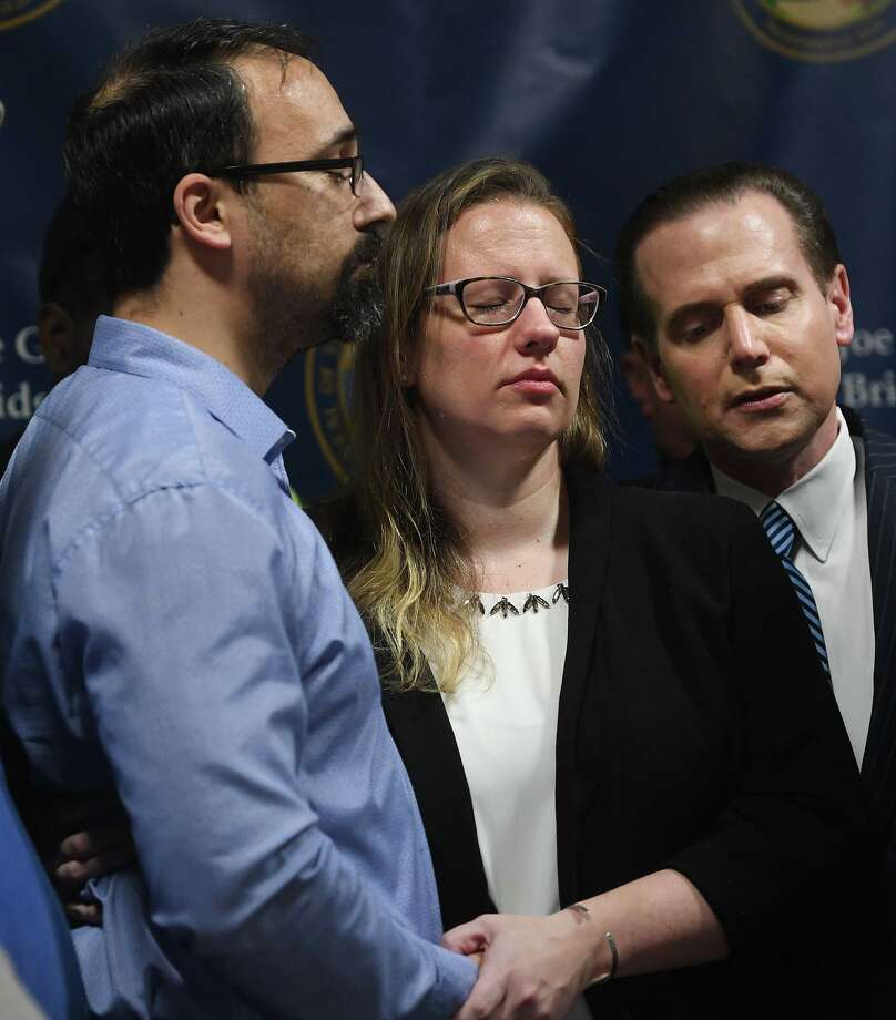 From left, Paul and Bunny Rodriguez, of North Branford; and News 12 reporter Frank Recchia, Rodriguez's uncle, bow their heads in prayer during a press conference at the Margaret Morton Government Center in Bridgeport Tuesday. The body of Bunny Rodriguez's missing father, Peter Recchia of Middletown, was discovered Sunday in a wooded area in Wallingford. Photo: Brian A. Pounds / Hearst Connecticut Media / Connecticut Post