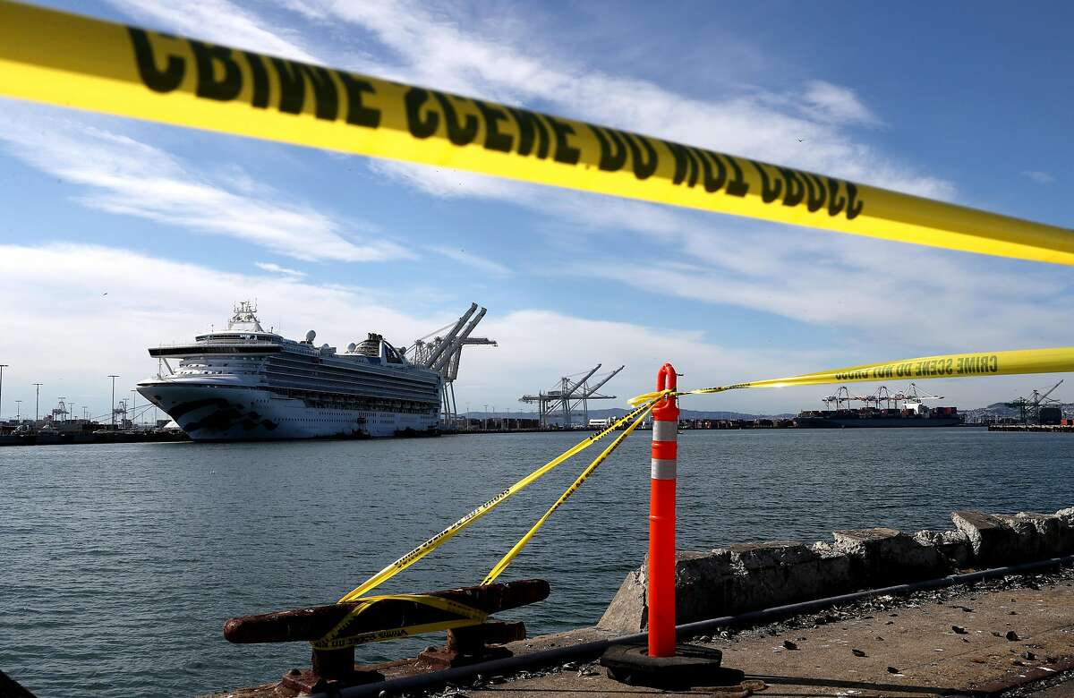 OAKLAND, CALIFORNIA - MARCH 10: Crime scene tape marks off the area where members of the media are staging near the Princess Cruises Grand Princess cruise ship as it sits docked in the Port of Oakland on March 10, 2020 in Oakland, California. Passengers are slowly disembarking from the Princess Cruises Grand Princess a day after it docked at the Port of Oakland. The ship was held off the coast of California after 21 people on board tested tested positive for COVID-19 also known as the Coronavirus. (Photo by Justin Sullivan/Getty Images)