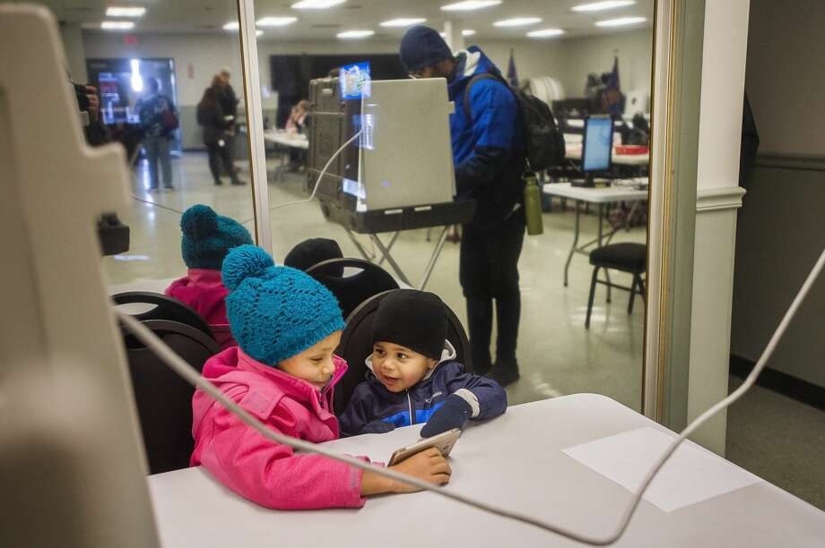 Addison Tryon, 7, and Adrian Tryon, 2, watch a video on their dad's phone as he casts his ballot in the presidential primary election Tuesday, March 10, 2020 at VFW Post 3651. (Katy Kildee/kkildee@mdn.net) Photo: (Katy Kildee/kkildee@mdn.net)