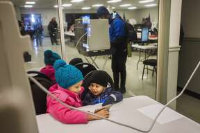 Addison Tryon, 7, and Adrian Tryon, 2, watch a video on their dad's phone as he casts his ballot in the presidential primary election Tuesday, March 10, 2020 at VFW Post 3651. (Katy Kildee/kkildee@mdn.net)