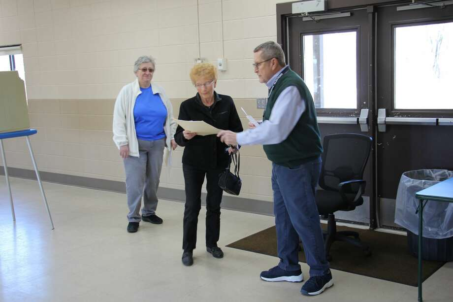 Election Inspector Dave Baxter is happy to assist Bad Axe voter Judith Muntz. Photo: Sara Eisinger/ Huron Daily Tribune