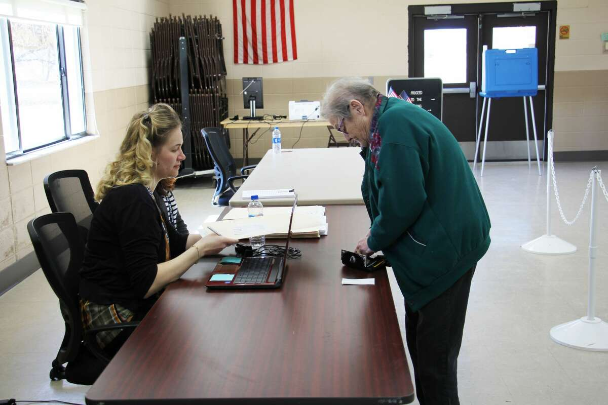 Election Inspector Rebecca Bachman assists Bad Axe voter Maxine Wolfe at the polls during a past election. The state primary will be held Aug. 4. (Tribune File Photo)