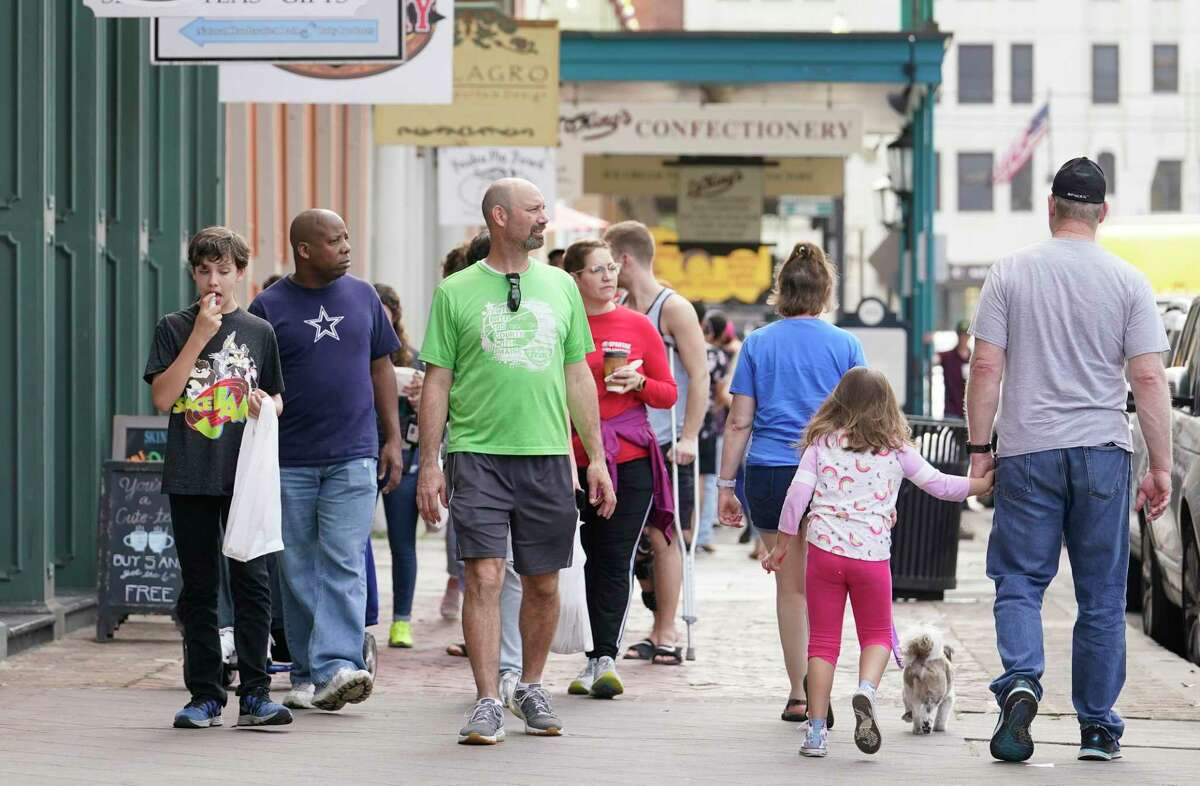 People walk along The Strand Tuesday, March 10, 2020, in Galveston.
