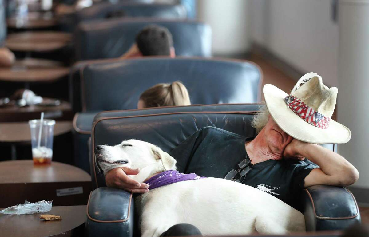 Larry Elmer Frederick and his dog, Soffiea Anne Dieffenbach, take an afternoon nap before venturing out for the evening at the Houston Livestock Show and Rodeo.