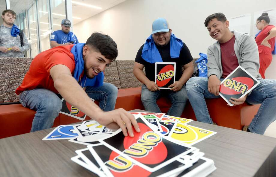 From left,Luis Rosales, Jose Barcenas and David Moreno joke with one another as they play a game of Uno Tuesday afternoon. In observance of National Student Appreciation Day, Lamar Institute of Technology held a student appreciation event with Chick-fil-A, snacks and oversized games at the Eagle's Nest. Photo taken Tuesday, March 10, 2020 Kim Brent/The Enterprise Photo: Kim Brent/The Enterprise