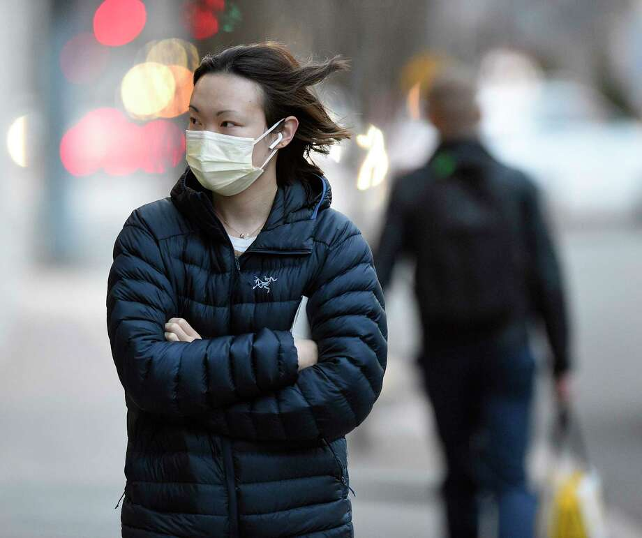 An unidentified female wears a protective mask as she walks down Broad Street on March 10, 2020 in Stamford, Connecticut. Earlier today Connecticut Gov. Ned Lamonte declared a State of Emergency as people and businesses react to the fear COVID-19 Coronavirus epidemic. Photo: Matthew Brown, Hearst Connecticut Media / Stamford Advocate
