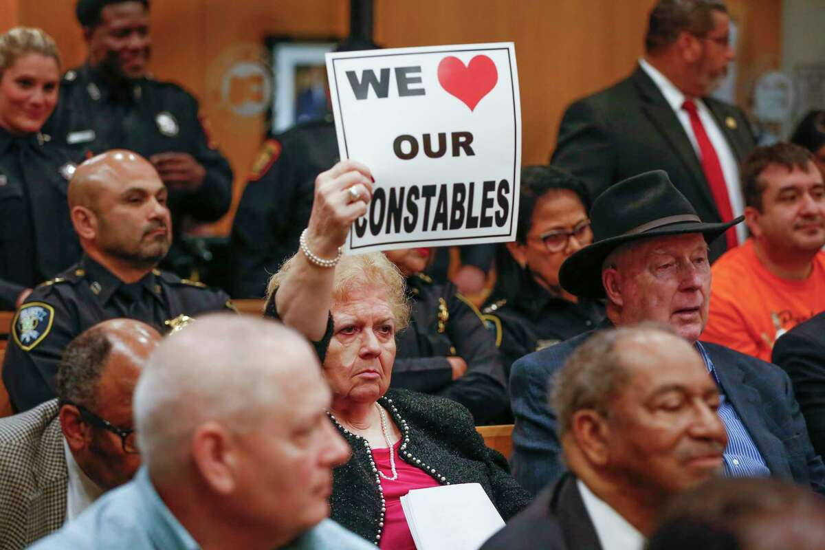 Harris County residents hold up signs of support as Harris County constables express their feelings regarding a proposed study of their contract deputy program during Tuesday's Commissioners Court meeting, March 10, 2020, in Houston.
