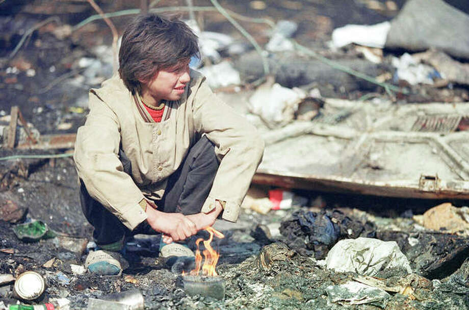 A boy trys to keep warm with a small fire in a trash dump in front of his house in Sarajevo on Wednesday, March 10, 1993. United Nations relief flights continue to arrive in Sarajevo but residents still struggle to keep warm and stay fed. (AP Photo/Michael Stravato)