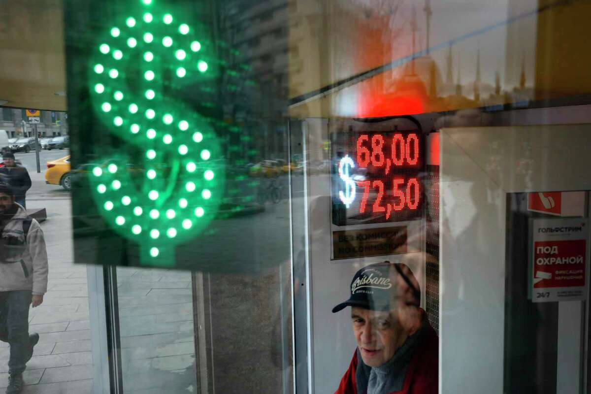 A man stands at an exchange office screen showing the currency exchange rates of U.S. Dollar and Euro to Russian Rubles in Moscow, Russia, Tuesday, March 10, 2020. Oil prices are plunging after Saudi Arabia started a price war against Russia. The Saudis tried to get the Russians to cut oil production to keep prices from falling even more due to the coronavirus.