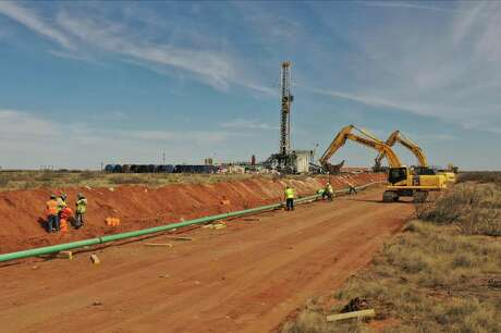 A pipeline is laid out near a drilling rig near Loving, N.M., in the Permian Basin.