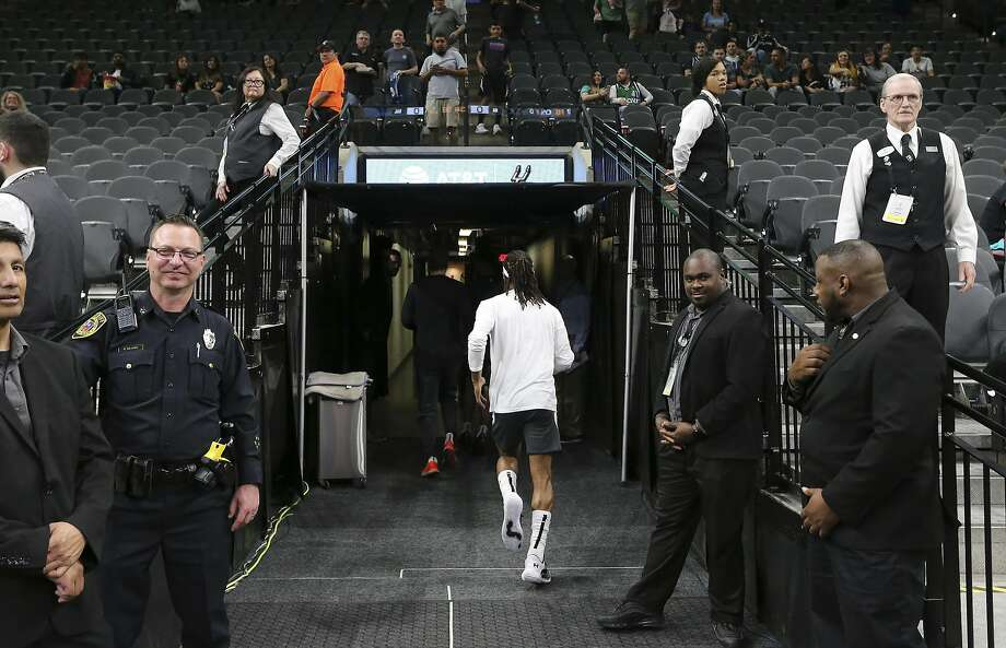 Spurs guard Patty Mills (center) runs toward the locker rooms after warmups before the game against the Dallas Mavericks on Tuesday, Mar. 10, 2020. The NBA has mandated new changes to the way players and coaches engage fans and media. For the San Antonio Spurs, Coach Gregg Popovich is now meeting media in an interview room instead of a scrum-type setting. Media are also no longer allowed in locker rooms post game. Players are also cautioned on how they engage with fans. Photo: Kin Man Hui, Staff Photographer