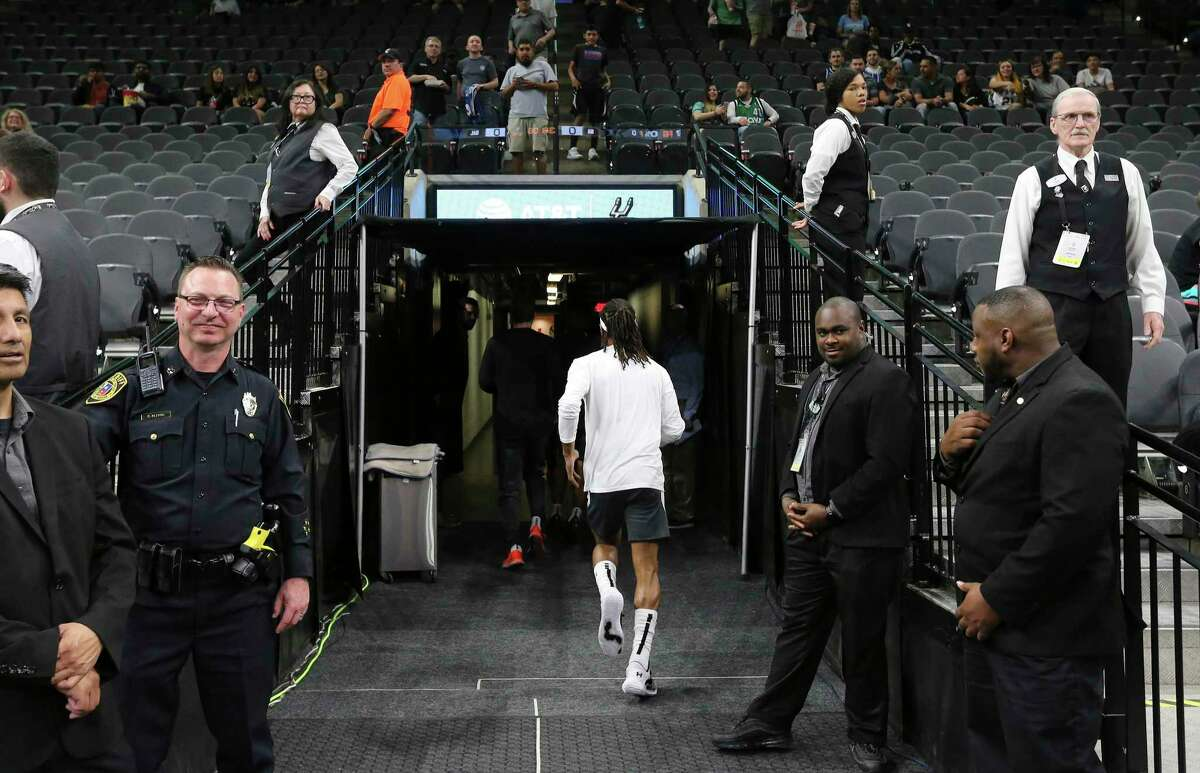 Spurs guard Patty Mills (center) runs toward the locker rooms after warmups before the game against the Dallas Mavericks on Tuesday, Mar. 10, 2020. The NBA has mandated new changes to the way players and coaches engage fans and media. For the San Antonio Spurs, Coach Gregg Popovich is now meeting media in an interview room instead of a scrum-type setting. Media are also no longer allowed in locker rooms post game. Players are also cautioned on how they engage with fans.