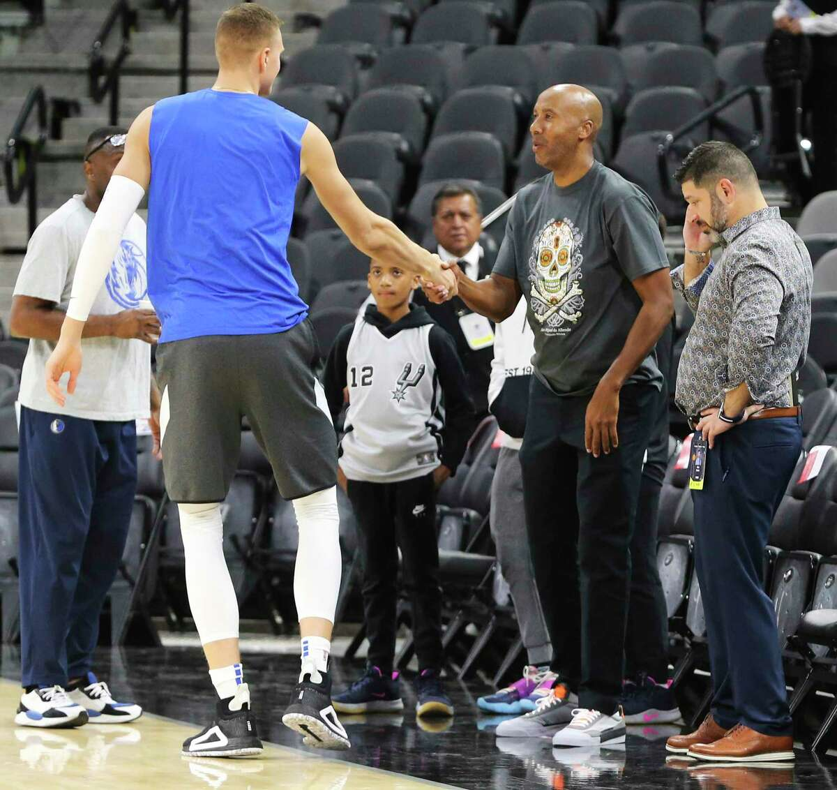 Ex-Spurs forward Bruce Bowen, right, shakes hands with Dallas' Kristaps Porzingis. Coaches and players say they trust the NBA's coronavirus guidelines.