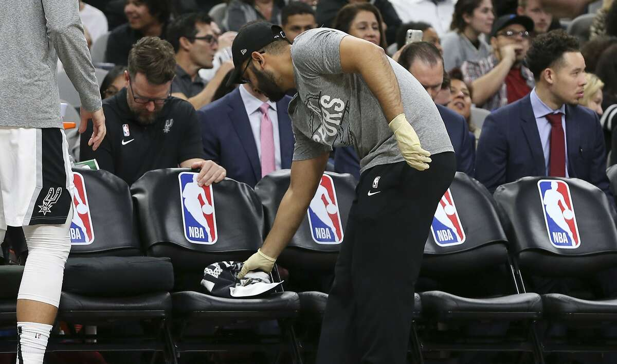 A Spurs attendant wears protective gloves and wipes off the players' bench in light of the Coronavirus concern during a timeout in the Spurs game against the Dallas Mavericks in the second half at the AT&T Center on Tuesday, Mar. 10, 2020. Spurs defeated the Mavs, 119-109.