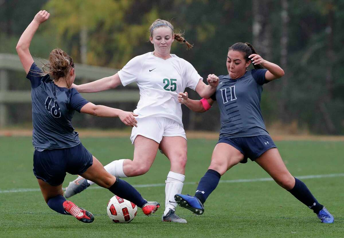 The Woodlands midfielder Gracie Britten (25) has her shot on broken up by Tomball Memorial midfielder Abby Wilson (18) and defender Serenity Martinez (11) in the second period of a match during the Lady Highlander Invitational at Gosling Sports Complext, Thursday, Jan. 2, 2020, in The Woodlands.