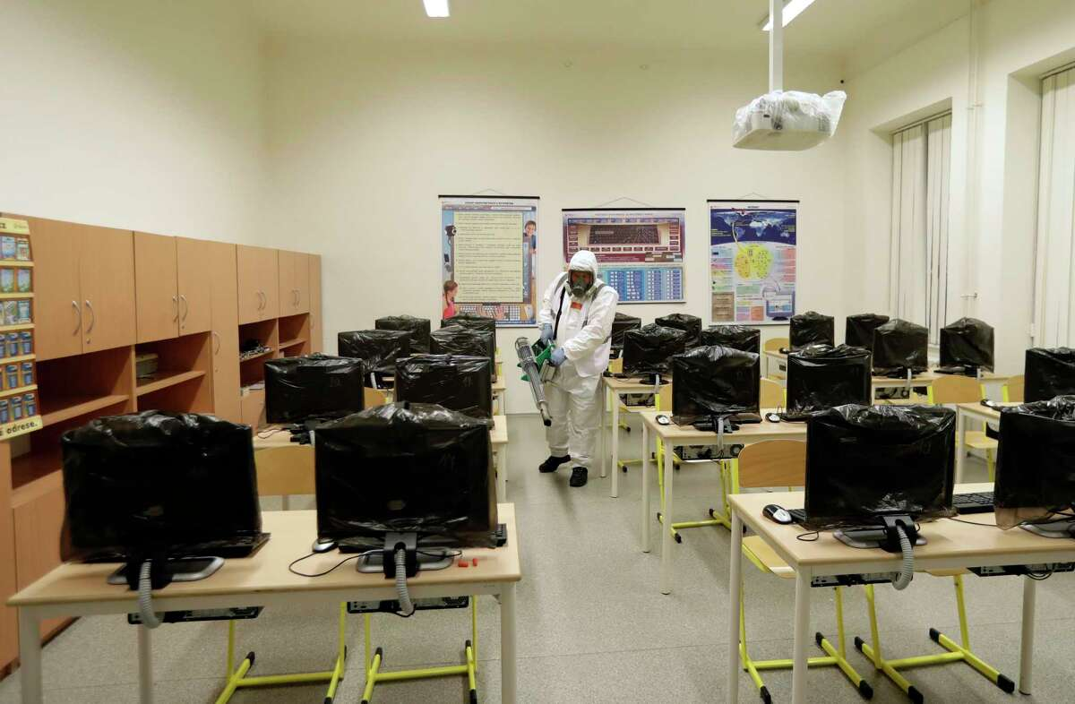 A worker disinfects a classroom at a closed school in Prague, Czech Republic, Tuesday, March 10, 2020. The Czech Republic is banning all public events with more than 100 people and is closing schools in response to the new coronavirus outbreak in Europe. For most people, the new coronavirus causes only mild or moderate symptoms, such as fever and cough. For some, especially older adults and people with existing health problems, it can cause more severe illness, including pneumonia. (AP Photo/Petr David Josek)