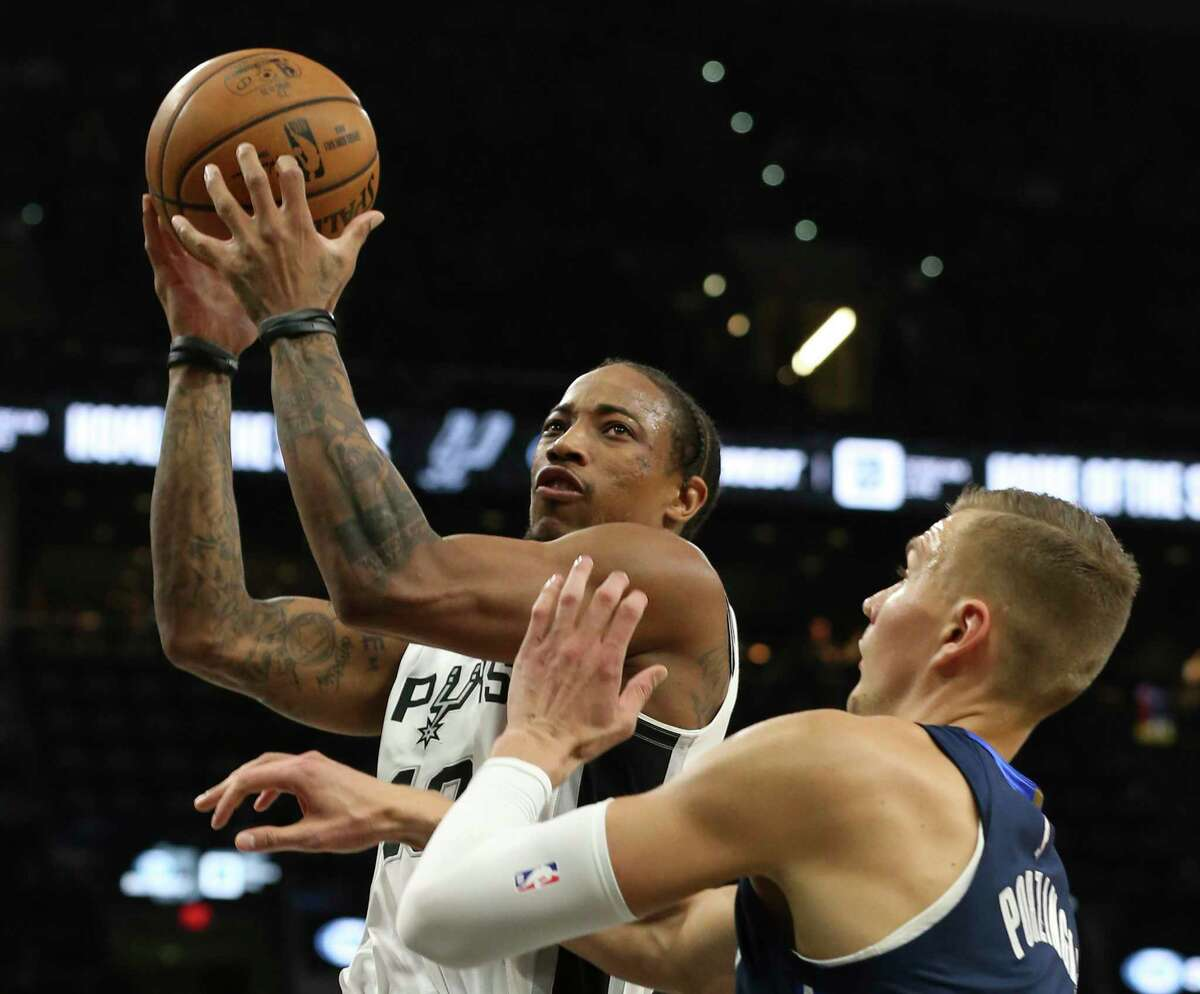 Spurs' DeMar DeRozan (left) goes toward the basket against Dallas Mavericks' Kristaps Porzingis (06) in the first half at the AT&T Center on Tuesday, Mar. 10, 2020.