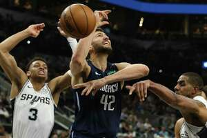 Spurs' Keldon Johnson (03) and LaMarcus Aldridge (right) jar the ball loose from Dallas Mavericks' Maxi Kleber (42) in the second half at the AT&T Center on Tuesday, Mar. 10, 2020. Spurs defeated the Mavs, 119-109.