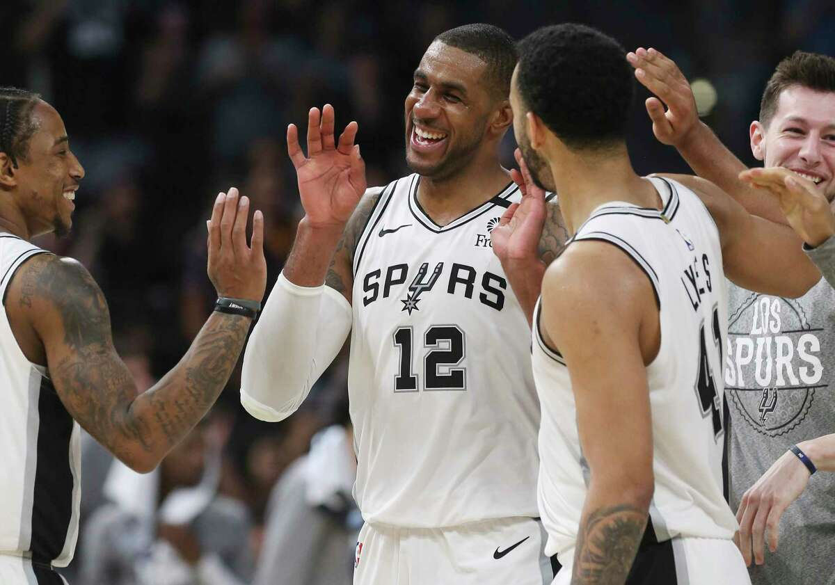 Spurs' LaMarcus Aldridge (12) reacts after a score with teammate DeMar DeRozan (left) and Trey Lyles (41) during the game against the Dallas Mavericks in the second half at the AT&T Center on Tuesday, Mar. 10, 2020. Spurs defeated the Mavs, 119-109.