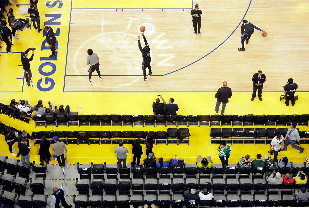 The Warriors warm up on the court watched by a sparsely populated crowd before the Golden State Warriors played the Los Angeles Clippers at Chase Center in San Francisco, Calif., on Tuesday, March 10, 2020.