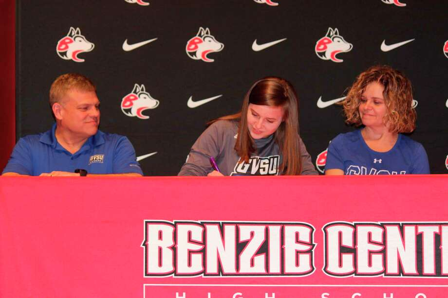 Surrounded by her parents Chip and Linda Johnston, Paige Johnston signs her letter of intent to continue her running career at Grand Valley State University, one of the premier NCAA Division 2 track and cross country programs in the nation. (Photo/Robert Myers)