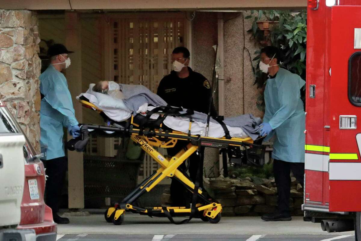 A patient is loaded into an ambulance, Tuesday, March 10, 2020, at the Life Care Center in Kirkland, Wash., near Seattle. The nursing home was at the center of the outbreak of the coronavirus in Washington state.