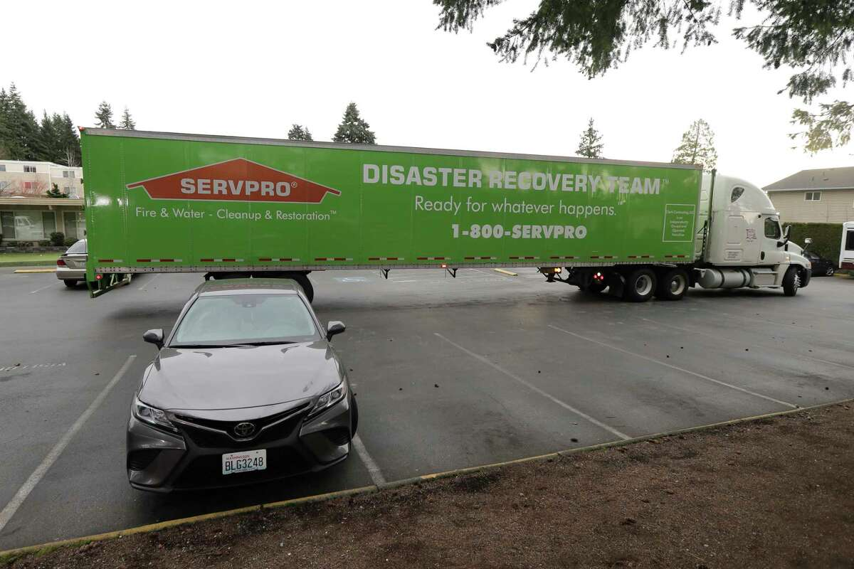 A semitrailer from a disaster cleanup company is backed into place, Tuesday, March 10, 2020, at the Life Care Center in Kirkland, Wash., near Seattle. The nursing home is at the center of the outbreak of the new coronavirus in Washington state.