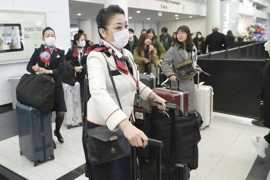Flight attendants wear protective masks as they walk through O'Hare International Airport in Chicago. Photo: Nam Y. Huh | AP