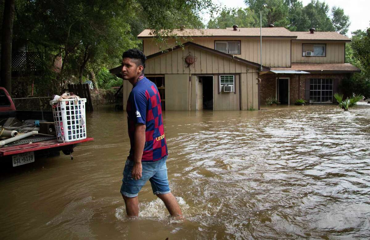 Alexander Sevilla walks outside his home waiting for his family who are on their way to help on Friday, Sept. 20, 2019, in New Caney. His home was flooded on Thursday after the torrential rains of Tropical Storm Imelda.