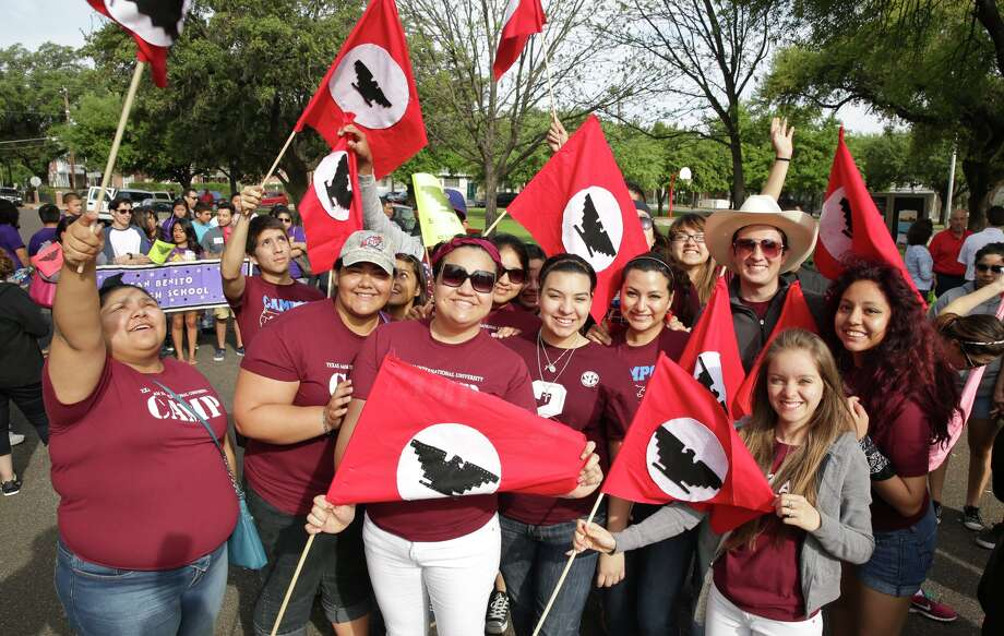 Members of the TAMIU College Assistance Migrant Program hold up their United Farm Workers of America flags, Saturday morning, in downtown Laredo during the 11th Annual Chesar Chavez's March for Justice. Photo: Victor Strife