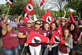 Members of the TAMIU College Assistance Migrant Program hold up their United Farm Workers of America flags, Saturday morning, in downtown Laredo during the 11th Annual Chesar Chavez's March for Justice.