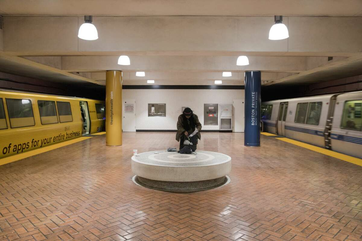 A passenger goes through their bag at the Montgomery BART station during rush hour in San Francisco, Calif. on March 10, 2020. The numbers of commuters on mass transit has dropped noticeably because of the coronavirus, which has prompted many employees to encourage workers to stay at home.