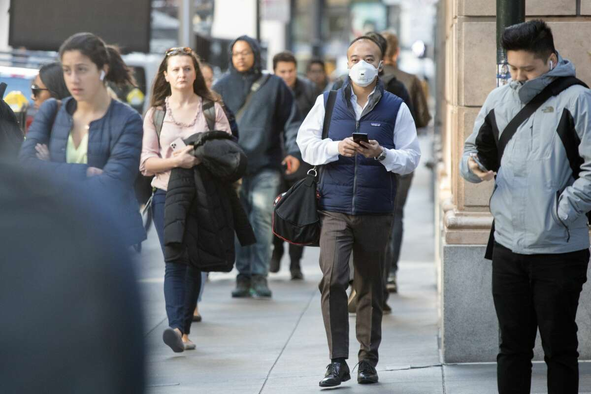 A man wears a protective mask walking down Montgomery Street during rush hour in San Francisco, Calif. on March 10, 2020. The streets in the Financial District were less packed because of the coronavirus, which has prompted many employees to encourage workers to stay at home.