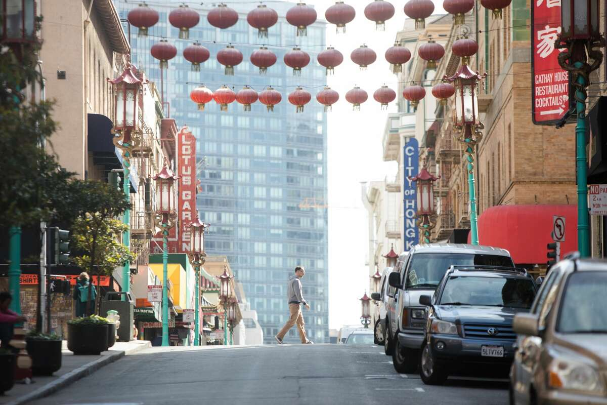A pedestrian crosses an empty Grant Ave in Chinatown in San Francisco, Calif. on March 10, 2020.