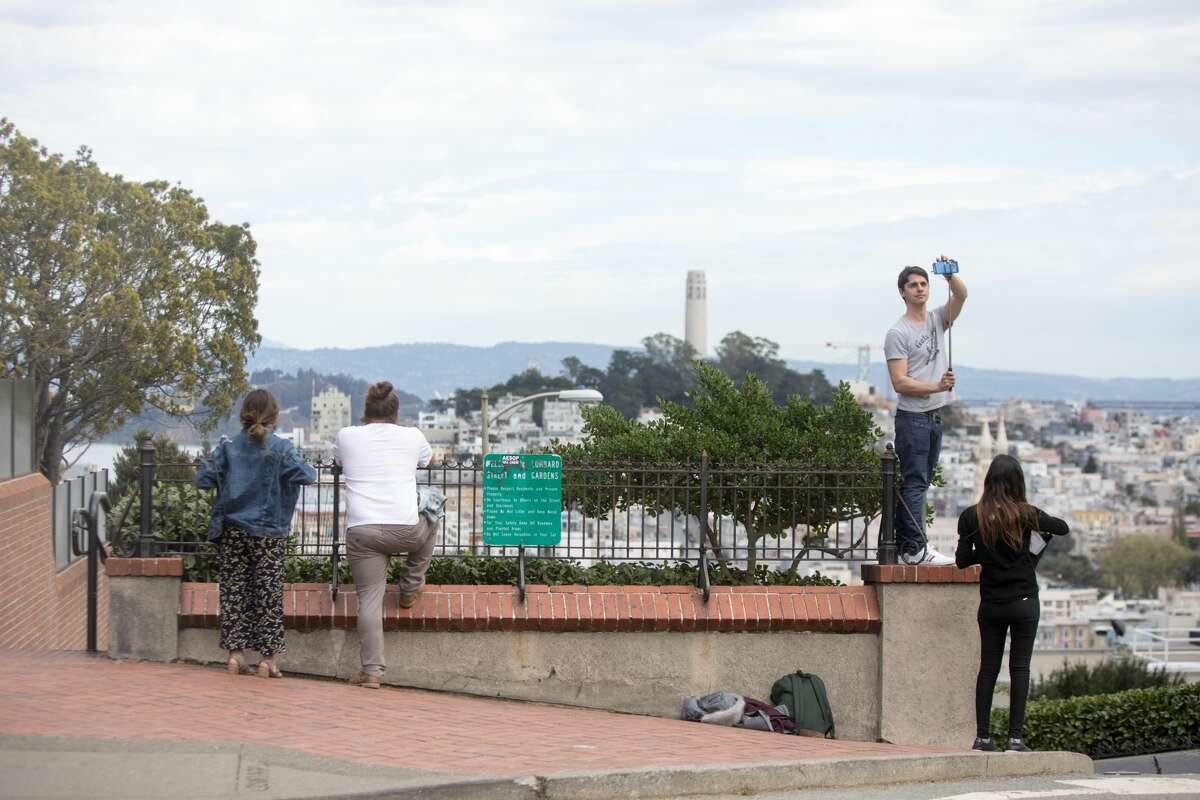 Visitors pose for photos on top of a quiet Lombard Street in San Francisco, Calif. on March 10, 2020. Tourist numbers are down in the city because of coronavirus concerns and the cancelation of tours from Asian and European visitors to San Francisco.