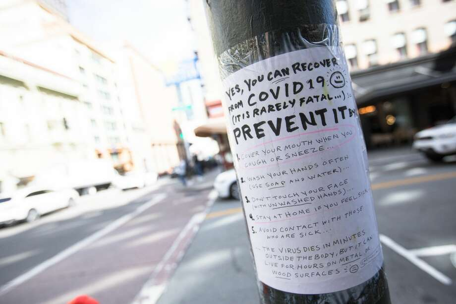 A handmade sign on Grant Ave. in San Francisco, Calif. on March 10, 2020 explains how to contain the COVID-19 coronavirus. The streets of San Francisco were noticeably more quiet because of the coronavirus, which has prompted many employees to encourage workers to stay at home. Photo: Douglas Zimmerman/SFGate.com