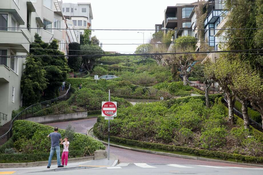 A family poses for a photo in front of a quiet Lombard Street in San Francisco, Calif. on March 10, 2020. Tourist numbers are down in the city because of coronavirus concerns and the cancelation of tours from Asian and European visitors to San Francisco. Photo: Douglas Zimmerman/SFGate.com