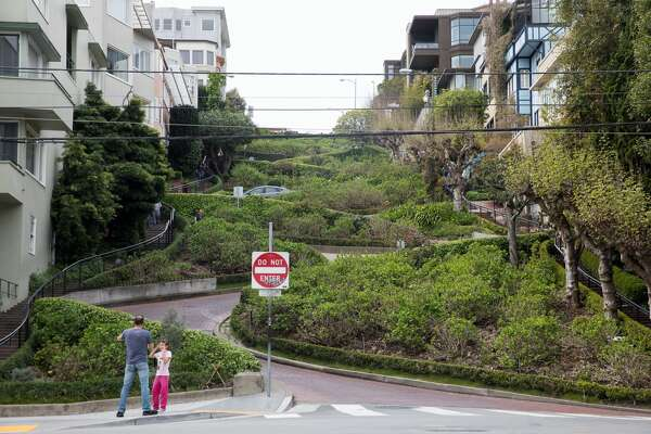A family poses for a photo in front of a quiet Lombard Street in San Francisco, Calif. on March 10, 2020. Tourist numbers are down in the city because of coronavirus concerns and the cancelation of tours from Asian and European visitors to San Francisco.