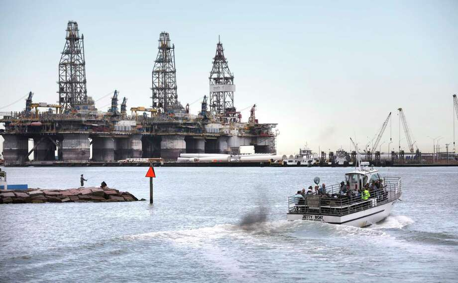 A jetty boat leaves the Port Aransas Marina and passes by massive offshore oil derricks across the ship channel on Harbor Island. The funky beach town is pushing back against a plan to dredge for supertankers and build berths across the ship channel. Photo: Bob Owen / ©2020 San Antonio Express-News