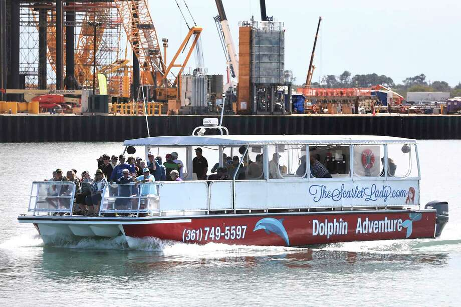 The Dolphin Adventure boat makes its way down the shipping channel past new oil terminal construction near Ingleside. Photo: Bob Owen / ©2020 San Antonio Express-News
