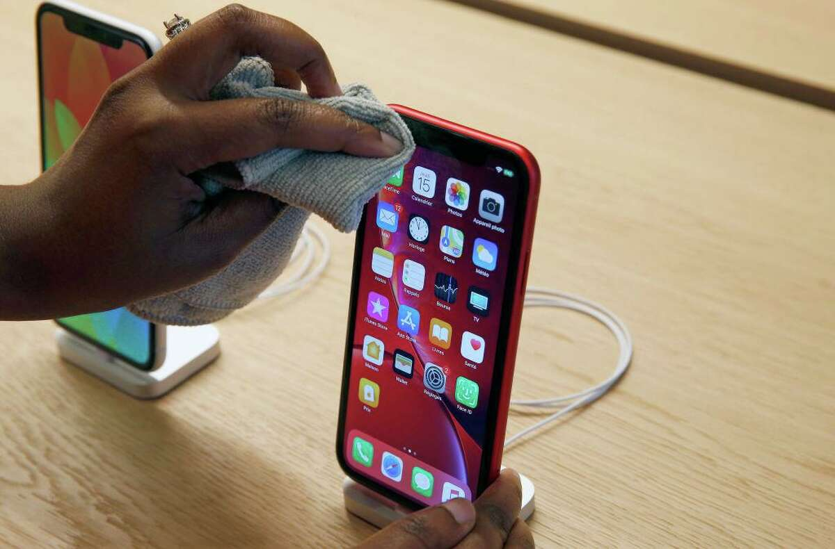 An employee cleans an iPhone Apple XR during the press visit of the new Apple Store Champs-Elysees on November 15, 2018 in Paris, France. Apple has changed its advice on how to clean its smartphones and other screens, saying users can now use disinfecting wipes.
