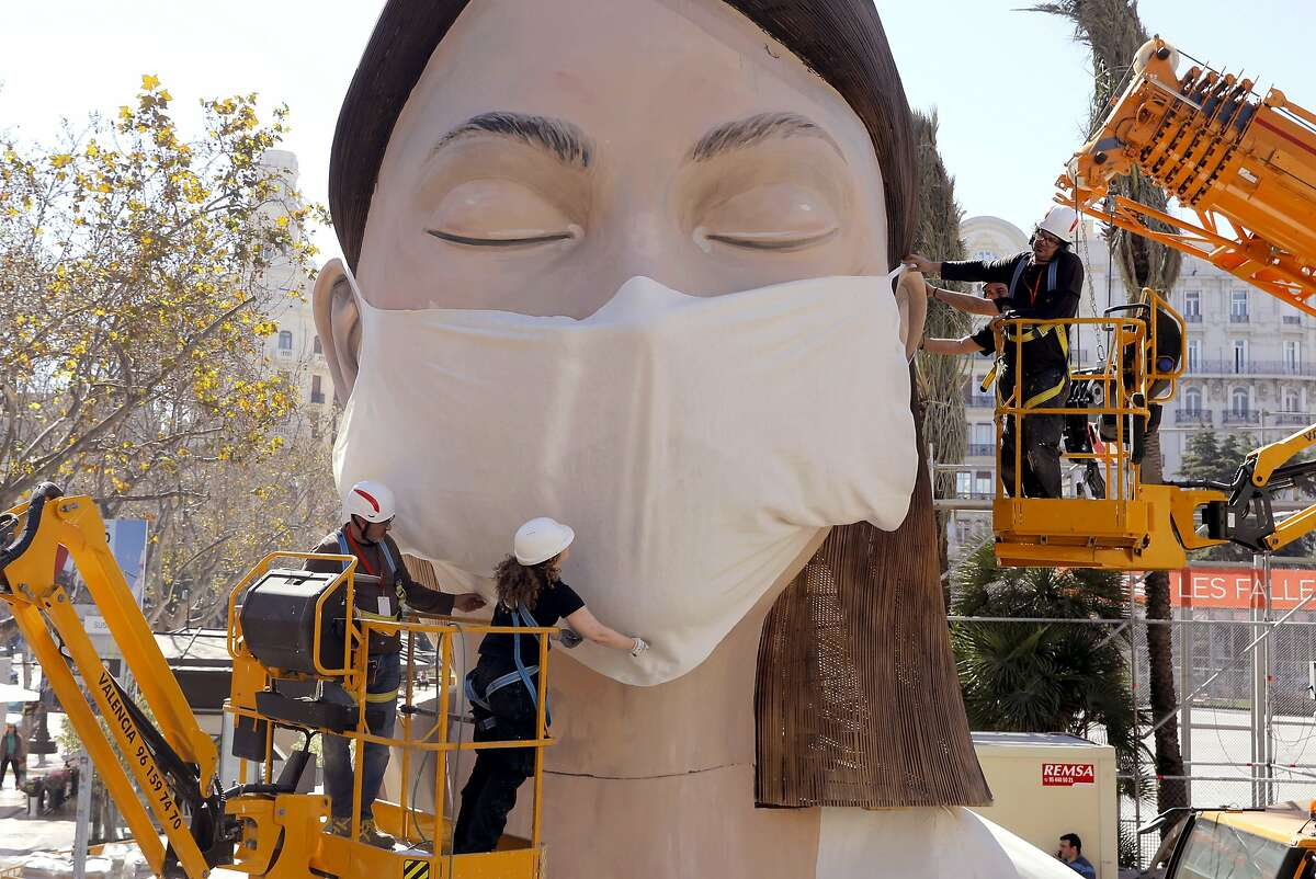 Workers place a mask on the figure of the Fallas festival in Valencia, Wednesday March 11, 2020. The Fallas festival which was due to take place on March 13 has been cancelled over the coronavirus outbreak. For most people, the new coronavirus causes only mild or moderate symptoms, such as fever and cough. For some, especially older adults and people with existing health problems, it can cause more severe illness, including pneumonia. (AP Photo/Alberto Saiz)
