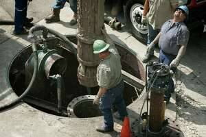 San Antonio Water System workers and other contractors remove a section of pipe 110 feet long from a well in downtown San Antonio in April 2006. City officials are asking SAWS and CPS Energy, the city's power utility, to temporarily stop disconnecting services for residents who fail to pay their bills during the coronavirus health emergency.