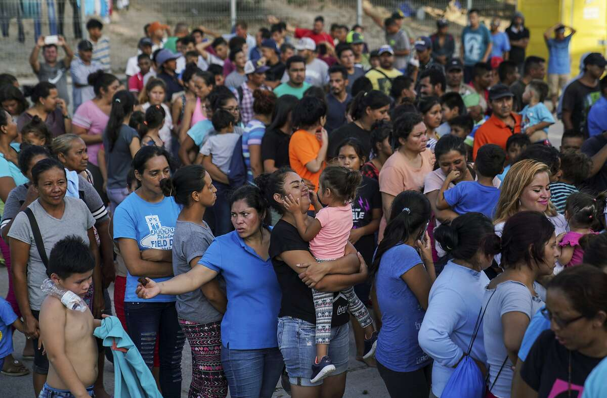 """FILE - In this Aug. 30, 2019, file photo, migrants, many who were returned to Mexico under the Trump administration's """"Remain in Mexico,"""" program wait in line to get a meal in an encampment near the Gateway International Bridge in Matamoros. In the latest twist for a signature Trump administration immigration policy, a federal appeals court said it is halting a policy next week to make asylum-seekers wait in Mexico for court hearings in the United States. But the U.S. 9th Circuit Court of Appeals in San Francisco said Wednesday, March 4, 2020, that it would only block the """"Remain in Mexico"""" policy in Arizona and California, the two border states where its authority extends. (AP Photo/Veronica G. Cardenas, File)"""