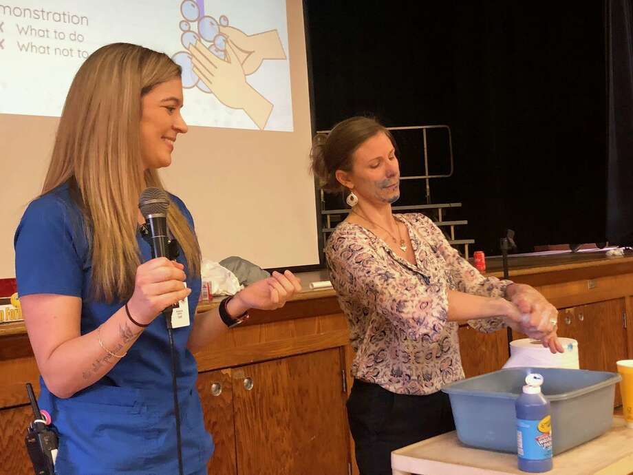 Booth Hill School physical education teacher Nicole Swercewski, right, demonstrates how to best wash hands as school nurse supervisor Adrianna Collins talks to students at the school's assembly Wednesday, March 11. Photo: Brian Gioiele / Hearst Connecticut Media / Connecticut Post