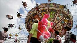 Rich Hargett stands in line for the Big Top Swinger ride with a pink dragon he won for his daughter, Holly, at the Houston Livestock Show and Rodeo, Wednesday, March 11, 2020, at NRG Center in Houston. Hargett, who traveled from Louisiana for the event, was eating when the people next to them said the rodeo would be closing. The rodeo will remain open until 4pm Wednesday.