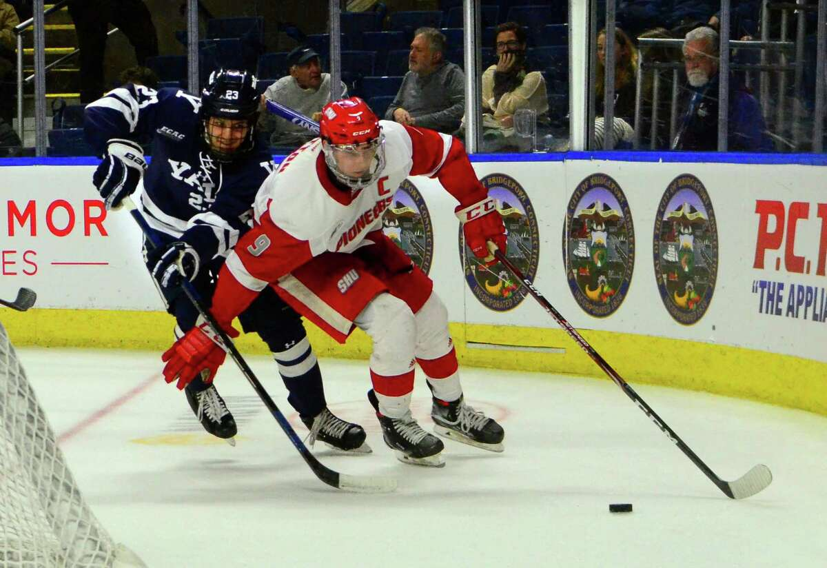 Sacred Heart University's Jason Cotton (9) intercepts the puck in front of Yale's Cole Donhauser during the Connecticut Ice Tournament last year in Bridgeport.
