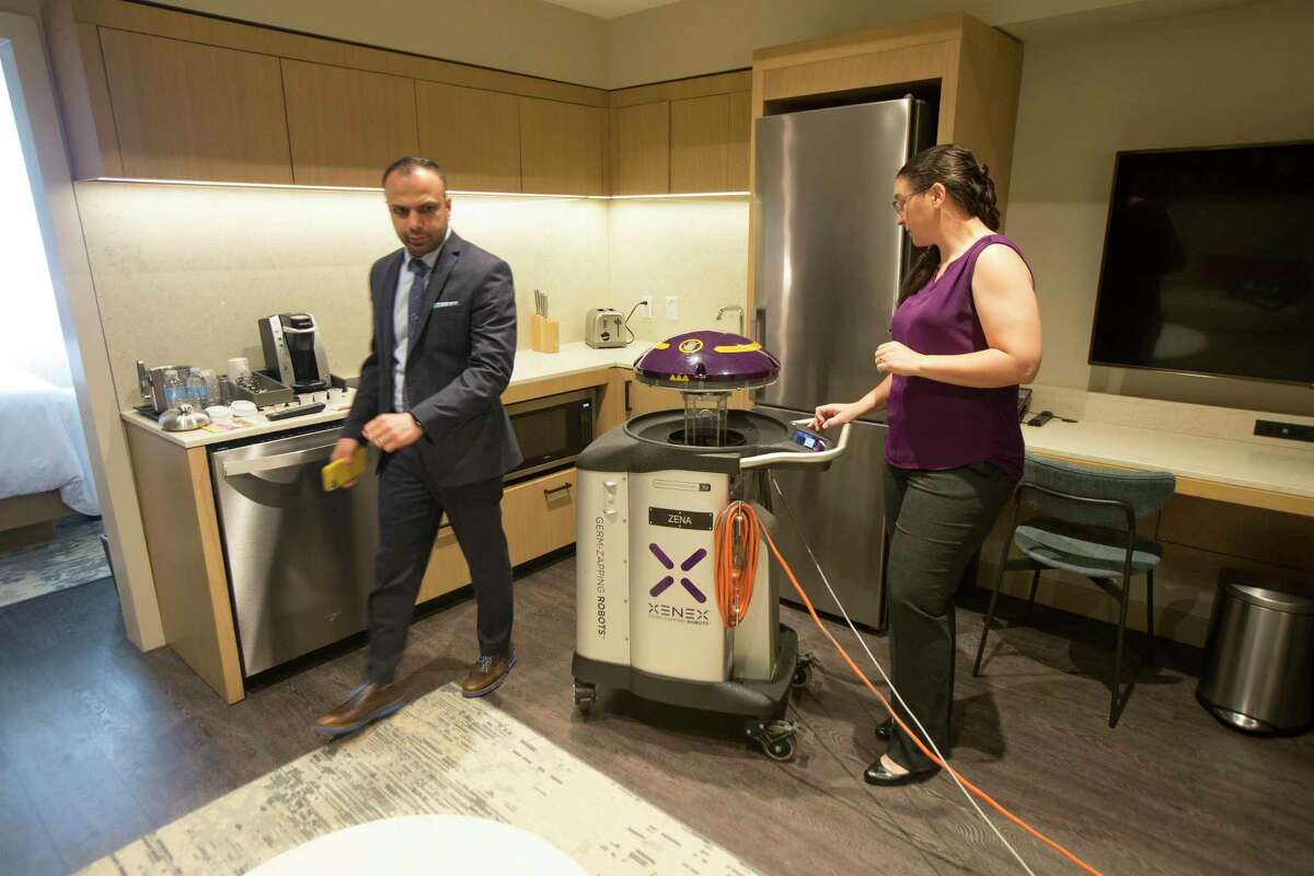 Archit Sanghvi, vice president of operations for Houston-based Pearl Hospitality, owner and manager of The Westin Houston Medical Center and Dr. Sarah Simmons, senior director of science for Xenex Disinfection Services demonstrates one of the two germ-fighting cleaning robots being used at The Westin Houston Medical Center to sanitize and disinfect guest rooms and common areas against the threat of coronavirus Wednesday, March 11, 2020, in Houston.